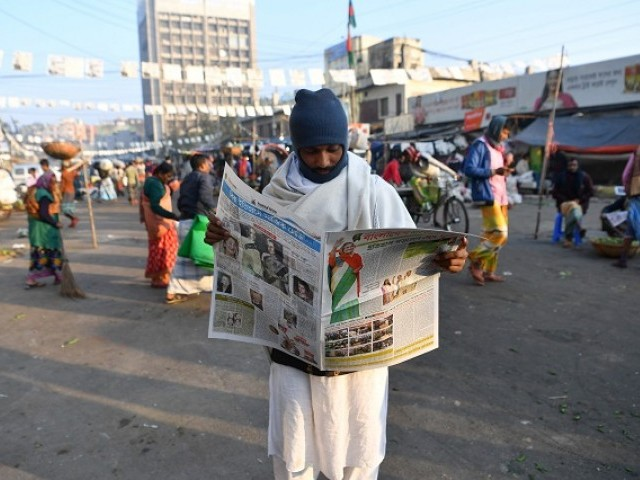 A Bangladeshi man reads a newspaper carrying headlines of the general election results in Dhaka on December 31, 2018. PHOTO:AFP