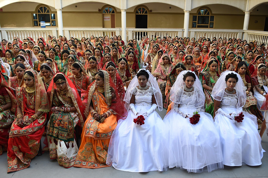 In this photo taken on December 23, 2018 Indian brides pose before a mass wedding in Surat, some 270km from Ahmedabad. - 261 women without fathers were married to partners in a mass wedding organized by the charitable PP Savani & Movaliya Groups. The majority were married in Hindu ceremonies, while 3 Christian and 6 Muslims women were included. PHOTO: AFP