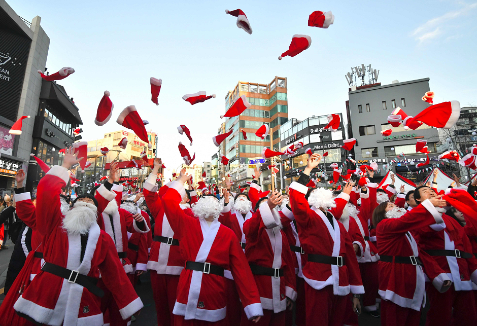 South Korean volunteers in Santa Claus outfits throw Santa hats during a ceremony before the delivery of Christmas gifts in Seoul on December 24, 2018. - The volunteers will deliver Christmas gifts to 1,200 kids from 800 poor families in Seoul on Christmas eve. PHOTO: AFP
