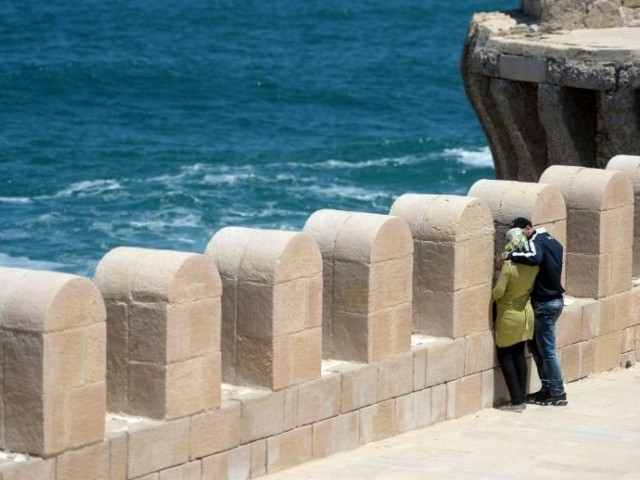 An Egyptian couple embracing during a stroll on Pharos Island in the port of Alexandria. PHOTO: AFP