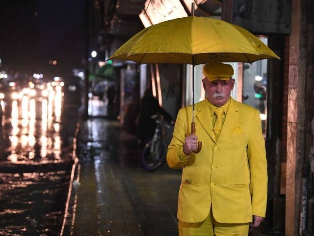 Abu Zakkour known as the Yellow Man, a symbol of peculiarity in the city, walks down the street in Aleppo, Syria. PHOTO: XINHUA