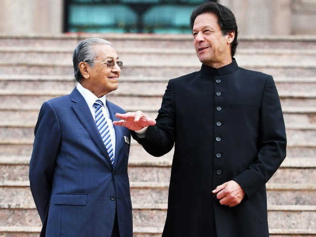 Malaysia's PM Mahathir Mohamad listens to Imran Khan during a welcoming ceremony at the prime minister's in Putrajaya. PHOTO: AFP