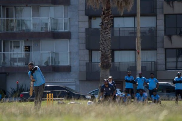 Indians living in Uruguay play a shot during a cricket match along Montevideo's seaside promenade. PHOTO: AFP