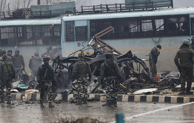 Indian security forces inspect the remains of a bus following an attack on a paramilitary Central Reserve Police Force (CRPF) convoy. -AFP