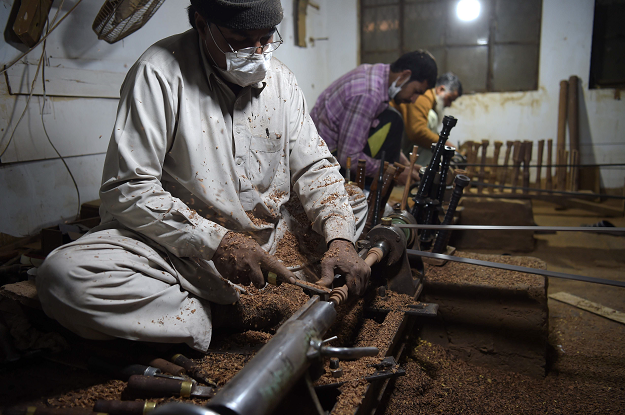 In this picture taken on January 25, 2019, Pakistani artisans work on machines to make components to be used in bagpipes at the Mid East bagpipe factory in the eastern city of Sialkot. PHOTO: AFP