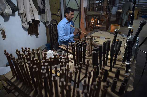 In this picture taken on January 25, 2019, a Pakistani worker makes components used in bagpipes at the Mid East bagpipe factory in the eastern city of Sialkot. PHOTO: AFP