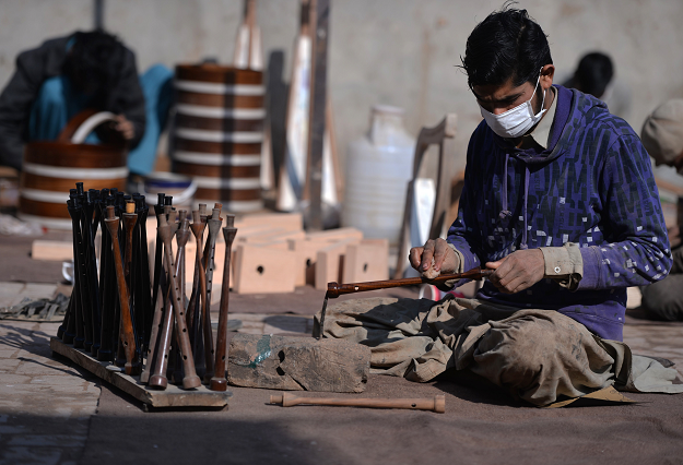 In this picture taken on January 25, 2019, a Pakistani worker polishes a component to be used to make a set of bagpipes at the Mid East bagpipe factory in the eastern city of Sialkot. PHOTO: AFP