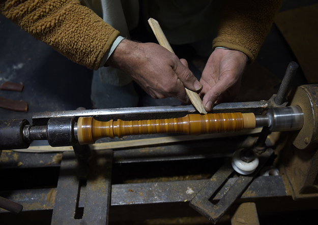 In this picture taken on January 25, 2019, Pakistani artisan works on a machine to make components to be used to make a set of bagpipes at the Mid East bagpipe factory in the eastern city of Sialkot. PHOTO: AFP