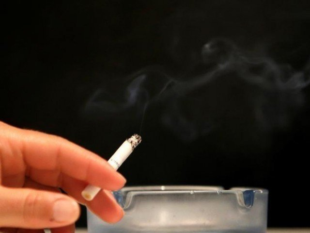 An individual smokes a cigarette in this representational image. PHOTO: REUTERS