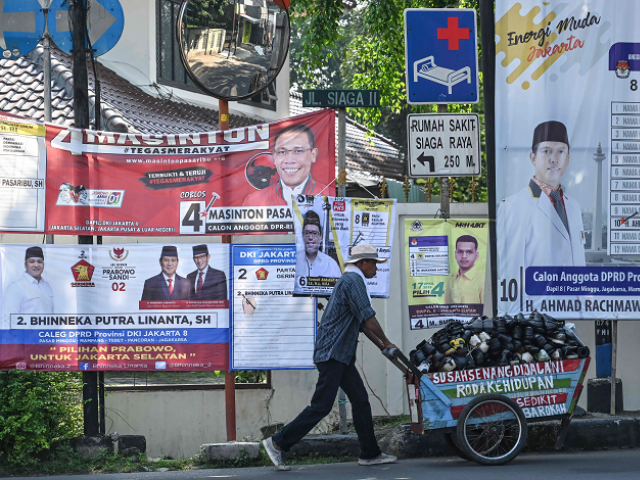 A man pushing a cart past election campaign banners in Jakarta. PHOTO: AFP