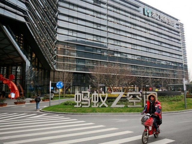 A man cycles past a building bearing the logo of MYbank, an online lender that is an offshoot of Alibaba at the Ant Financial Services headquarters, in Hangzhou, Zhejiang province, China January 24, 2018. PHOTO: REUTERS
