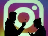 silhouettes-of-mobile-users-are-seen-next-to-a-screen-projection-of-instagram-logo-in-this-picture-illustration-2-2-2