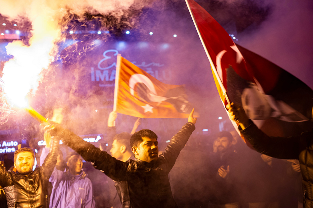 Supporters of the main opposition Republican People's Party (CHP) wave flags and light up torches to celebrate the local election in Istanbul. PHOTO: AFP