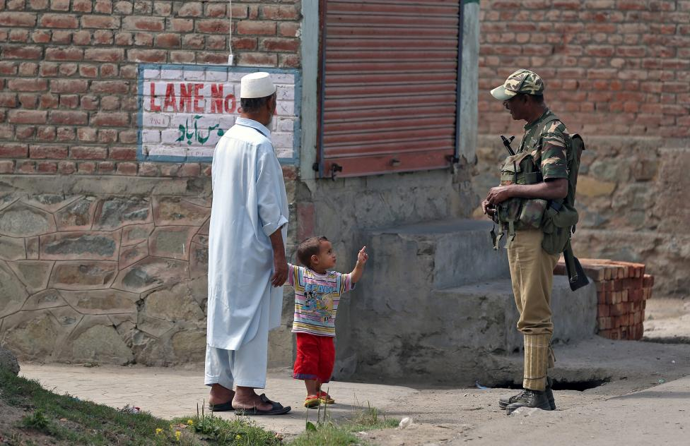 a-boy-gestures-at-a-member-of-the-security-forces-in-srinagar-as-the-city-remains-under-curfew-following-weeks-of-violence-in-kashmir-2