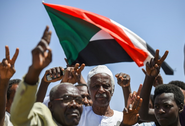 sudanese-protesters-wave-the-national-flag-at-the-sit-in-outside-the-army-headquarters-in-the-capital-khartoum-1