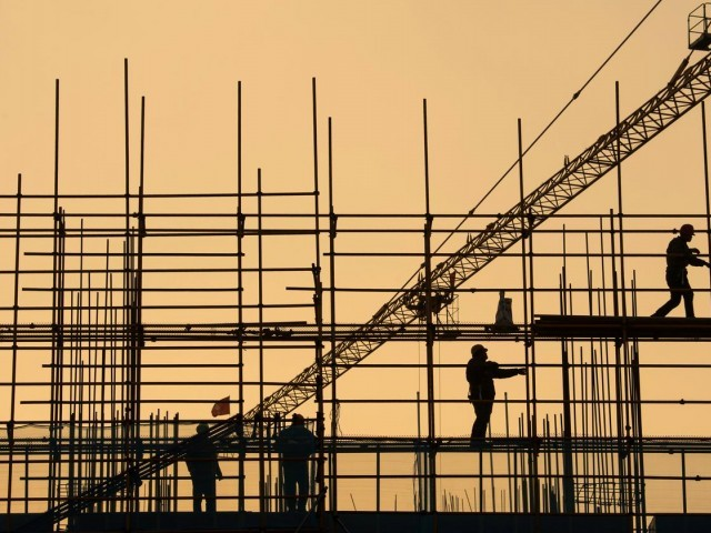 Workers are seen on scaffolding at a construction site. PHOTO: REUTERS