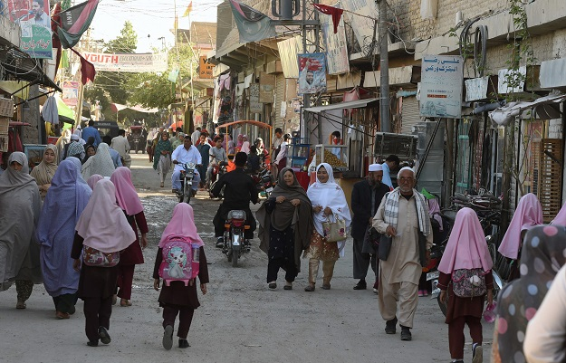 In this picture taken on May 3, 2019, Pakistani Hazara minority Muslims walk along a road in Hazara town, a neighbourhood in Quetta. PHOTO: AFP