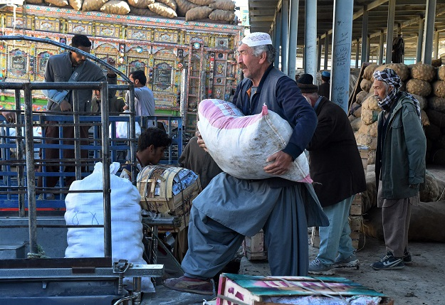 In this picture taken on April 18, 2019, Shiite Hazara minority traders load fruit and vegetables at a market before returning to their heavily guarded enclave where they live on the outskirts of Quetta. PHOTO: AFP