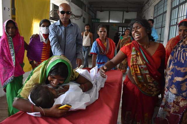 A child arrives in a hospital due to Acute Encephalitis Syndrome as family members react in Muzaffarpur, India, on June 10, 2019. PHOTO: AFP