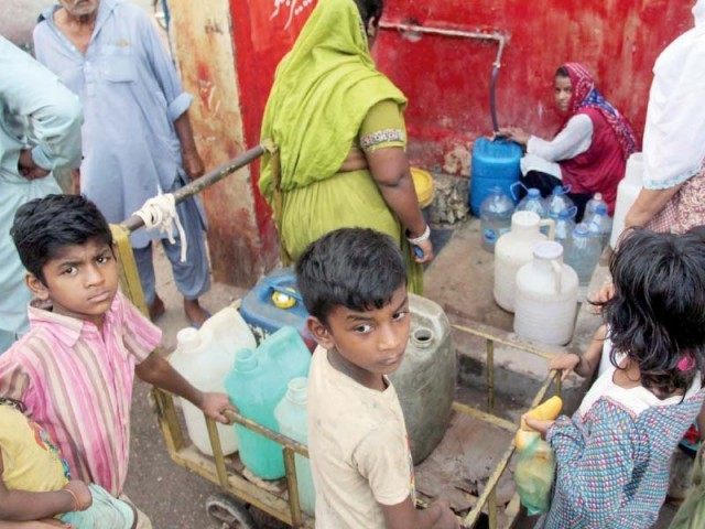 Women and children gather to collect water from a public tap in Bheempura. Water scarcity in the provincial capital remains a regular nuisance for the citizens of Karachi. PHOTO: ONLINE