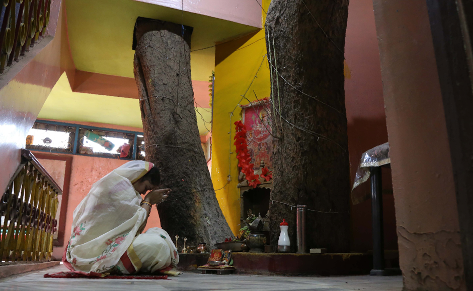Neelu Kesharwani, daughter-in-law of Moti Lal Kesharwani who built the house around a peepal tree (sacred fig tree), performs a ritual next to the tree on the second floor of their house in Jabalpur, in the Indian state of Madhya Pradesh. Photo: Reuters