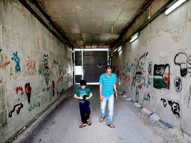 Palestinian Omar Hajajla walks with his son through the tunnel connecting their home in Jerusalem to al-Walajah, their village in the occupied West Bank, on May 30, 2019. PHOTO: AFP