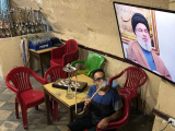 a-man-smokes-a-hookah-as-he-watches-lebanons-hezbollah-leader-sayyed-hassan-nasrallah-speak-on-television-inside-a-coffee-shop-in-the-port-city-of-sidon-lebanon