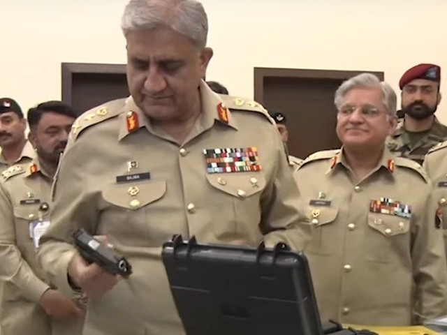 "COAS Gen Qamar inspects a locally-manufactured gun during a two-day national seminar titled ""Defence Production - Security through Self Reliance"", held at Army Auditorium in Rawalpindi. SCREENGRAB"