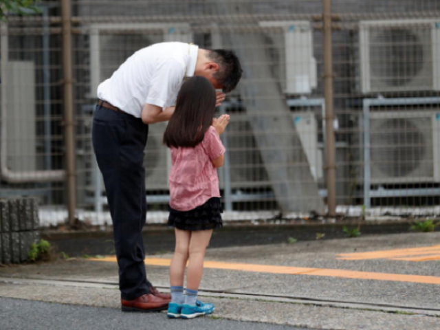 Father and daughter mourning the loss of victims in the Japan attack. PHOTO: Reuters