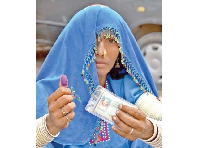 A woman shows her inked thumb after casting her vote for the NA-205 seat in Ghotki. The situation remained relatively peaceful in the constituency. PHOTO: APP