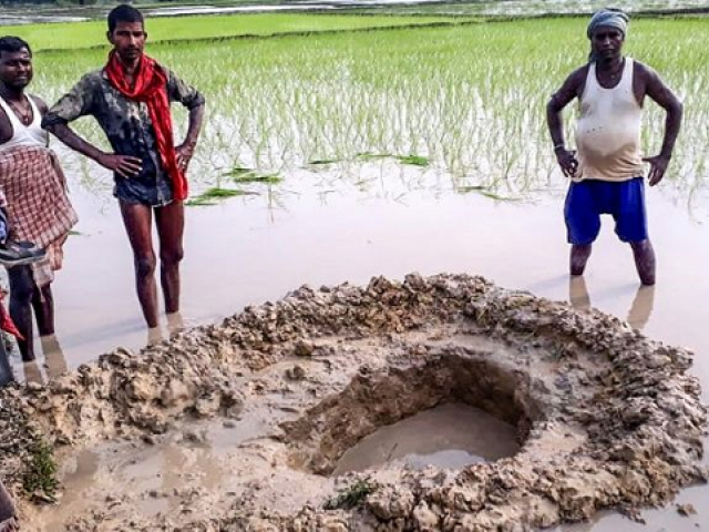 Villagers and farmers gather around the crater formed when a suspected meteorite crashed into a rice paddy in Madhubani district in India's Bihar state. PHOTO: AFP