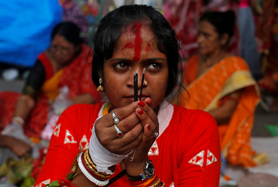 A woman worship Hindu goddess Bipadnashini during a religious ceremony in which married women fast for whole day for the betterment of their family in a temple premises in Kolkata, India:REUTERS