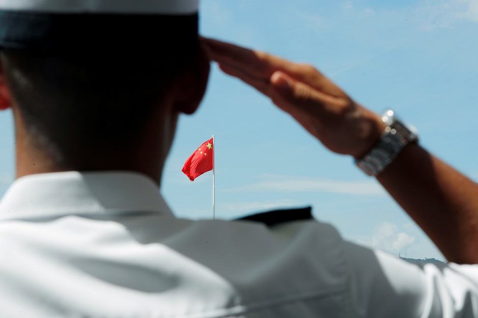 A People's Liberation Army (PLA) soldier saluts to Chinese national flag during an open day of Stonecutters Island naval base, in Hong Kong, China:REUTERS