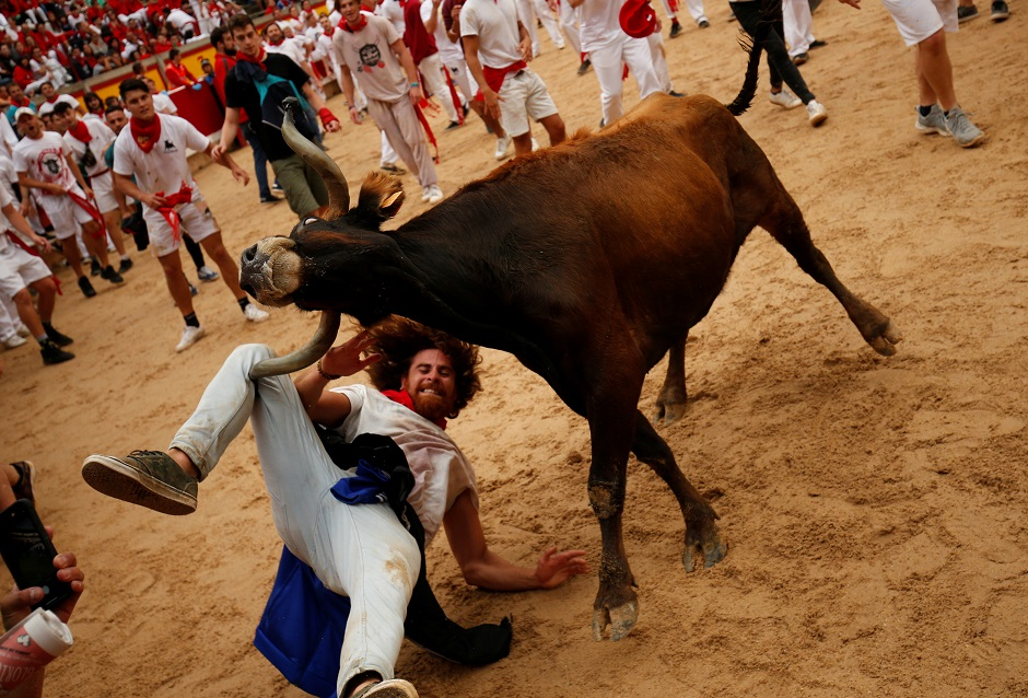 A bull hits a reveller as he fall down in the bull ring after the running of the bulls at the San Fermin festival in Pamplona:REUTERS