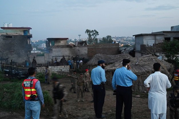Security officials gather at the scene where a Pakistani Army Aviation Corps aircraft crashed in Rawalpindi. PHOTO: AFP