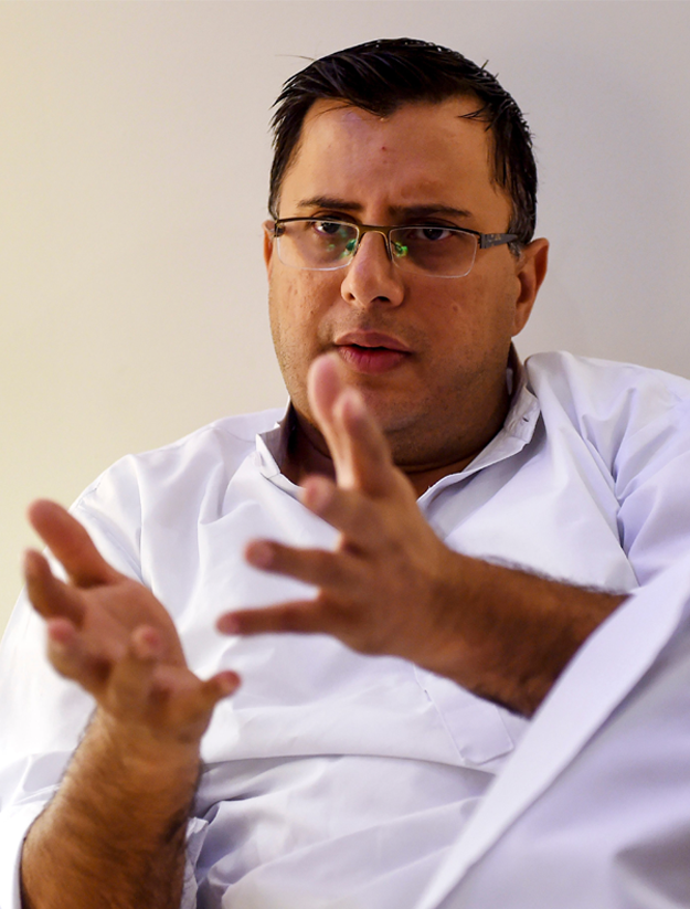 Pakistani police officer and crime stories writer Omar Shahid Hamid gestures as he speaks during an interview with AFP in Karachi. - Personal tragedy haunts the hard-boiled novels that are turning top cop Omar Shahid Hamid into one of Pakistan's most popular English-language authors