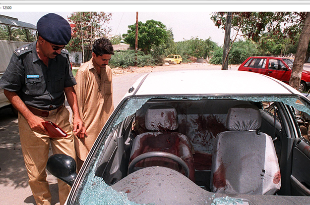 In this file photo taken on July 5, 1997, a police officer inspects the bullet-riddled car of Shahid Hamid, managing director of the state-run Karachi Electric Supply Corporation (KESC), who was killed along with his driver and guard by unidentidied gunmen in Karachi