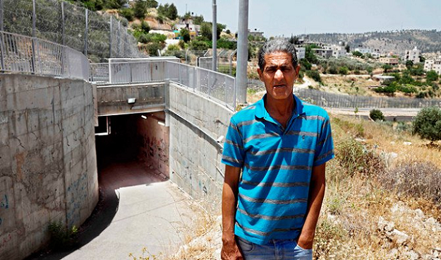 Palestinian Omar Hajajla poses next to the tunnel connecting his home in Jerusalem to al-Walajah, his village in the occupied West Bank, on May 30, 2019. PHOTO: AFP