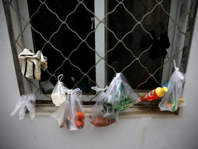 Groceries in plastic bags hang by a window. PHOTO: REUTERS