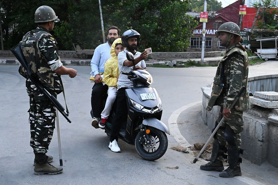 A motorist shows his identity card to a security personnel after being stopped for questioning at a roadblock during a lockdown in Srinagar. PHOTO: AFP
