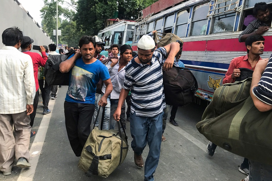In this picture taken on August 6, 2019 people arrive with their bags at the tourist centre to board buses to leave from Srinagar. PHOTO: AFP