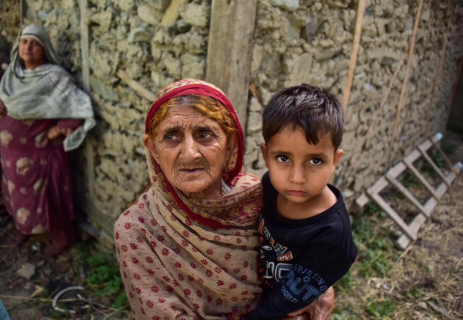 A Kashmiri woman holds a child as she looks on outside her a damaged house following recently cross border shelling at the Line of Control, the de facto border between Pakistan and India, in Neelum Valley of Pakistan-administered Kashmir. PHOTO: AFP
