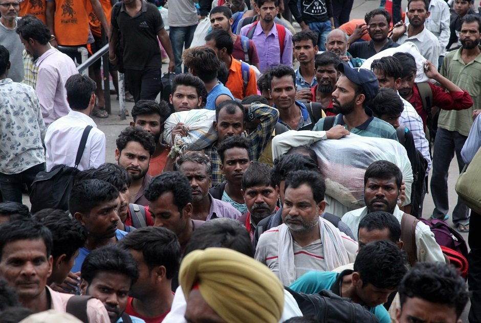 Labourers from across India working in Kashmir wait outside Jammu Railway Station as they leave to go back to their home states due to the heightened security situation in Jammu. PHOTO: AFP