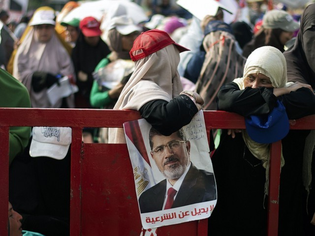 An Egyptian woman lean on a barrier as thousands of Muslim Brotherhood members and supporters of ousted President Mohamed Morsi gather in front of Rabaa al-Adawiya mosque in Cairo. PHOTO: AFP