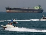 Iranian Revolutionary Guards drive speedboats in front of an oil tanker at the port of Bandar Abbas in this July 2, 2012 PHOTO: AFP/FILE