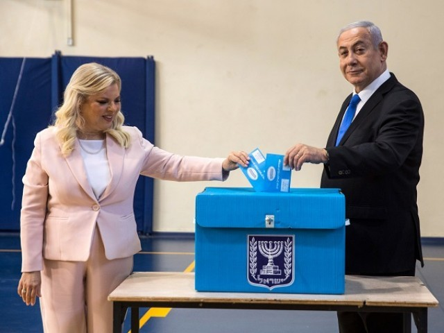Israeli Prime Minister Benjamin Netanyahu and his wife Sara casts their votes at a voting station in Jerusalem. PHOTO: AFP