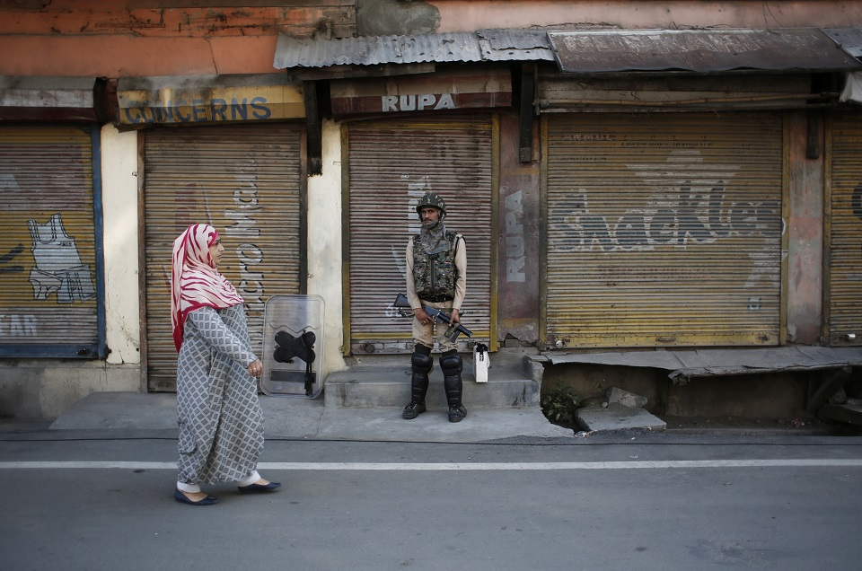 A Kashmiri woman walks past an Indian security personnel as he stands guard in front of closed shops. (PHOTO: REUTERS)