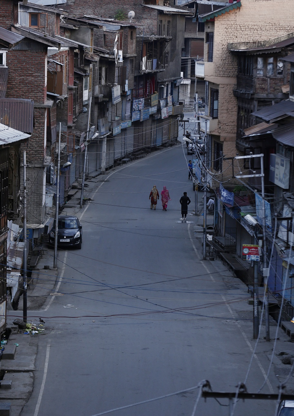Kashmiri women walk on a deserted road. (PHOTO: REUTERS)