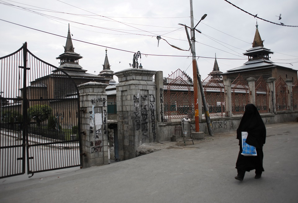 A Kashmiri woman walks past the locked Jamia Masjid (grand mosque). (PHOTO: REUTERS)