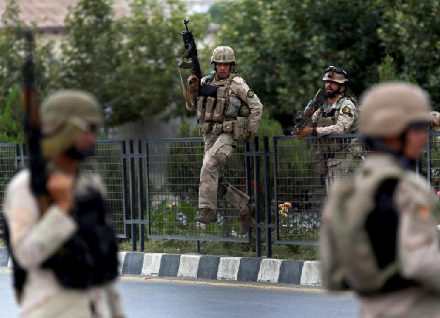 Members of Afghan security forces climb over a fence in Kabul Afghanistan
